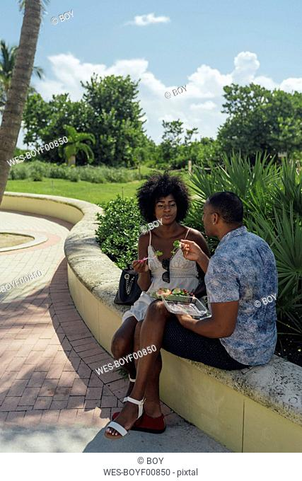 USA, Florida, Miami Beach, young couple sharing a salad in a park