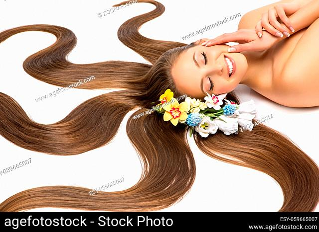 beautiful young woman with long hair lying on white floor. flowers. beauty studio shot. copyspace