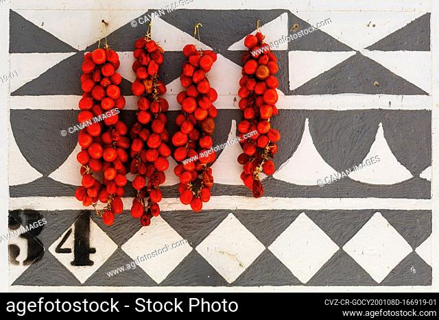 Tomatoes drying on a traditionally decorated wall of a house in Pyrgi