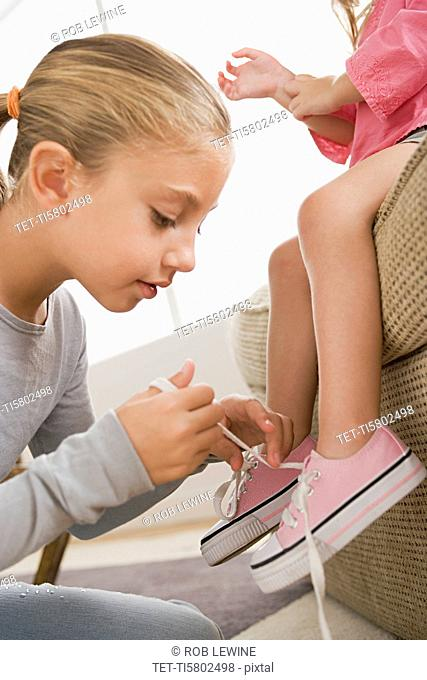 Girl 12-13 tying her younger sister's 8-9 shoes