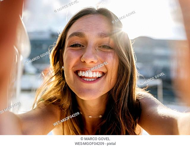 Young beautiful woman taking a selfie on a sailboat