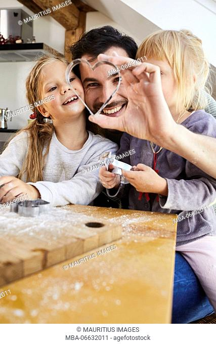 Family baking christmas cookies, father and daughters having fun, looking trough cookie cutter, portrait