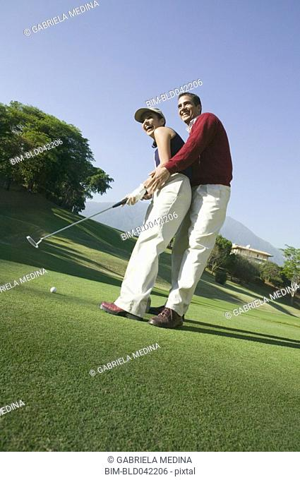 Hispanic couple playing golf