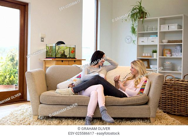 Young woman lying with her legs over her partner and a cup of coffee. The couple are talking and smiling