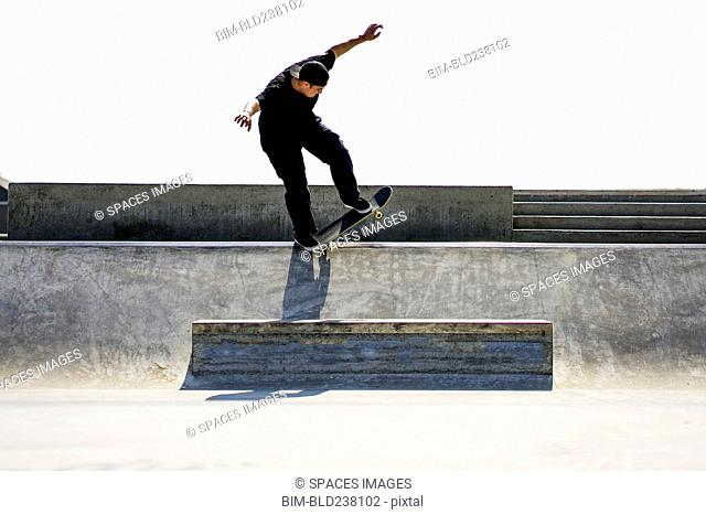 Caucasian man riding skateboard in skate park
