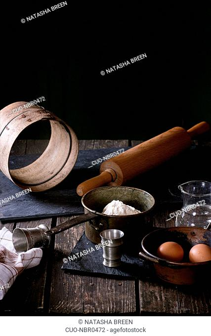 Ingredients for dough making. Flour, eggs in vintage copper bowls and salt with sieve and rolling-pin over old wooden table. Rustic style