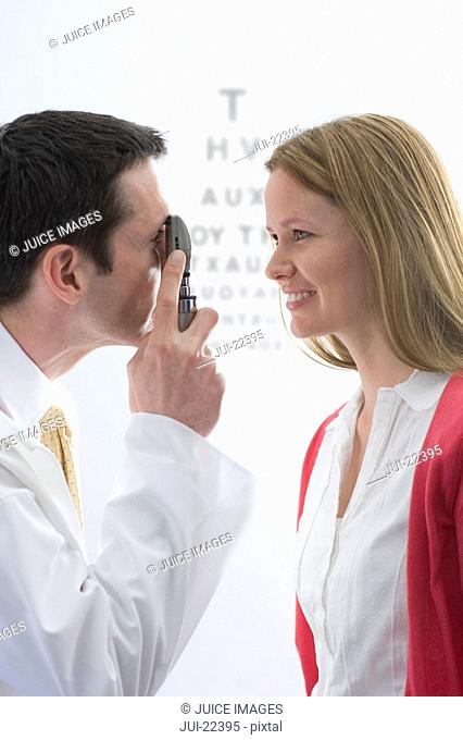 Doctor examining female patients eyes with ophthalmoscope