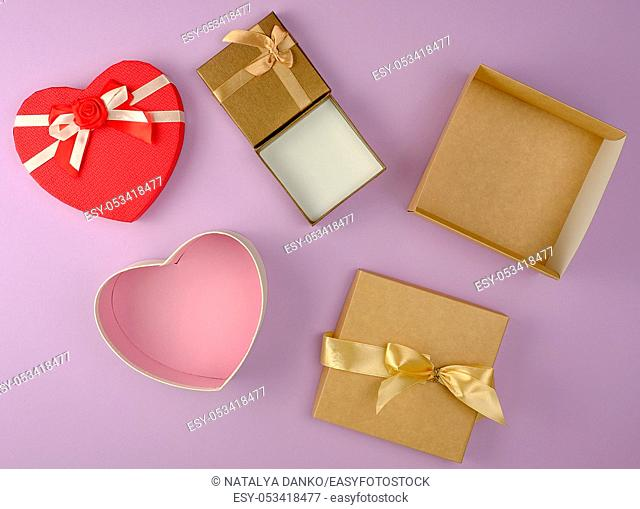 various empty open paper gift boxes on purple background, top view, festive backdrop