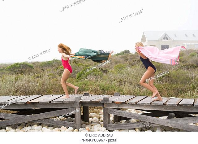 Two girls running on a boardwalk
