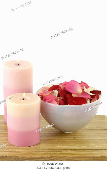 Candles lit up near rose petals in a bowl