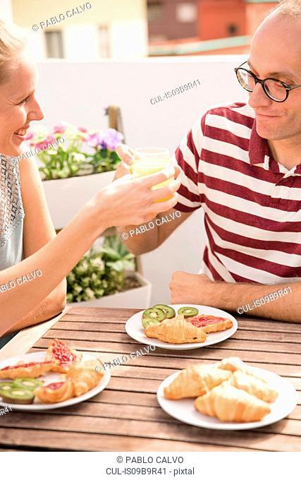 Young woman handing breakfast orange juice to boyfriend at patio table