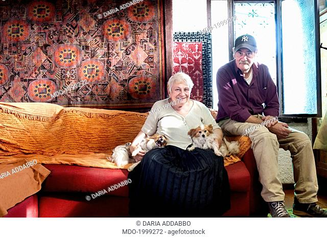 Old woman and man sitting on the sofa in their livingroom with their dogs. Lido dei Pini, Anzio (Italy), 6th June 2014
