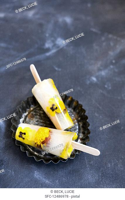 Lolly pops with flowers in a baking tray on a black background