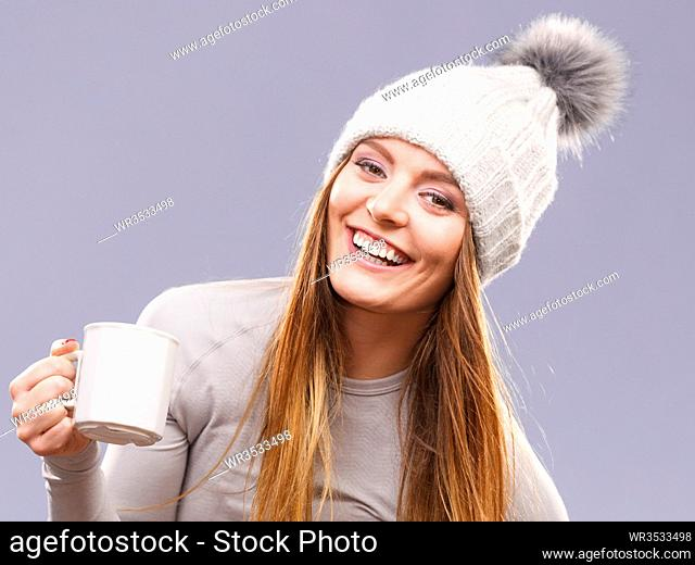 Attractive woman long hair girl in winter wool cap holds mug with tea hot beverage, warming herself studio shot on gray