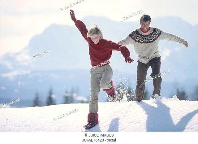 View of a young couple walking in the snow