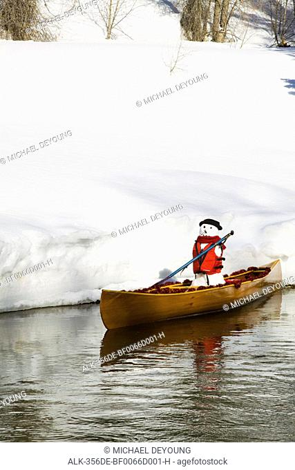 Snowman wearing a life jacket appears to canoe along the Conejos River, Colorado, Winter