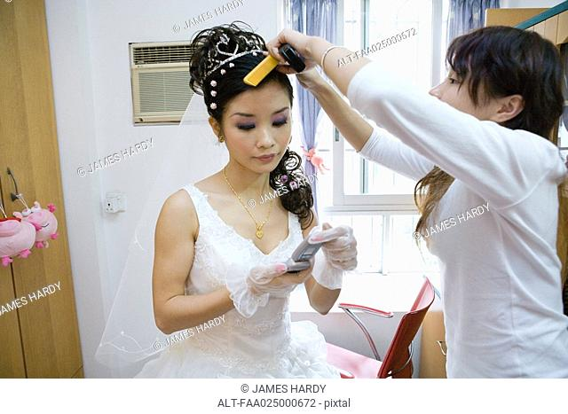 Bride having her hair styled by friend, looking down at cell phone