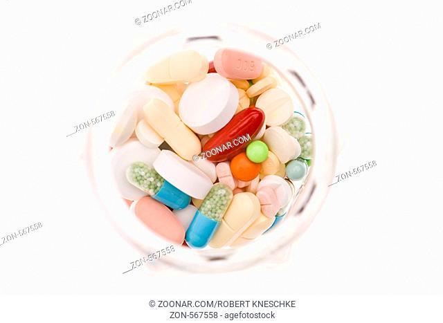 Blick von oben in ein Glas voller bunter Medikamente