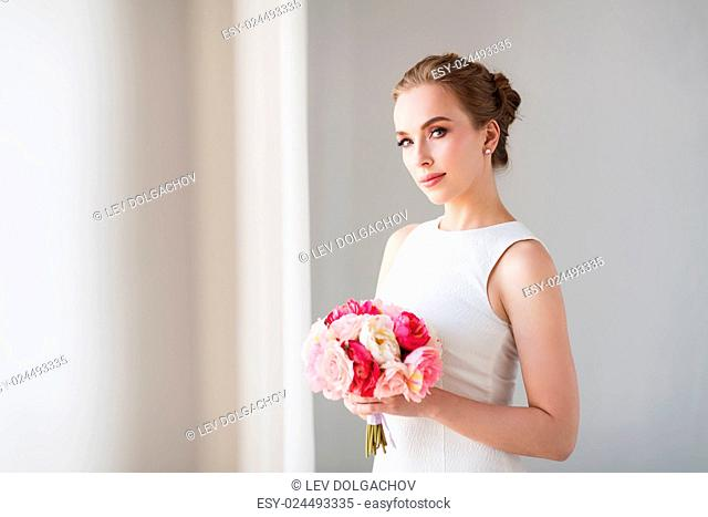 holidays, wedding and people concept - bride or woman in white dress with flower bunch