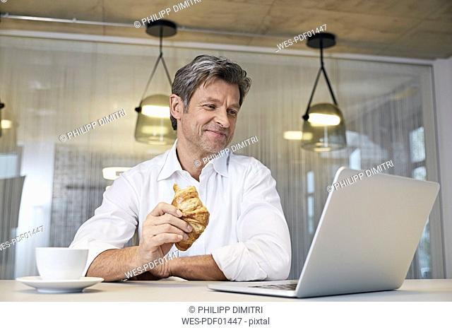 Businessman using laptop while eating croissant