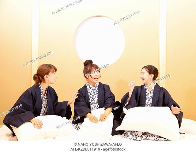 Young Japanese women wearing yukata at traditional ryokan inn bedroom