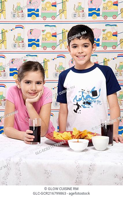 Portrait of a boy and girl with a platter of nachos