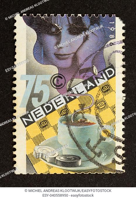 HOLLAND - CIRCA 1980: Stamp printed in the Netherlands shows a woman and a warm cup of coffee, circa 1980