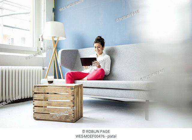 Smiling woman sitting on couch using tablet