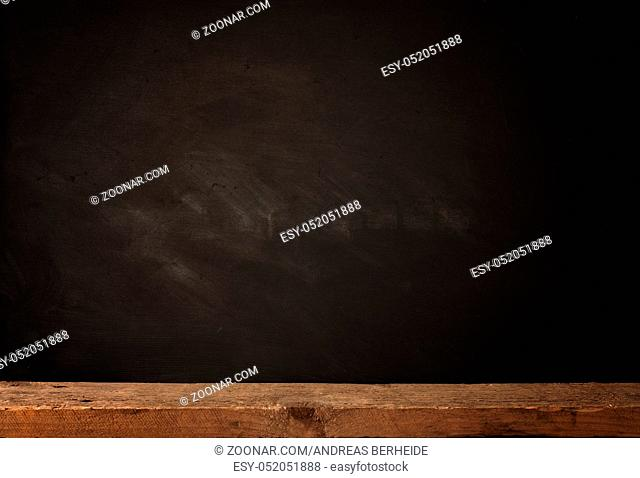 Rustic wooden table with a blank chalkboard, concept background with space for text or image