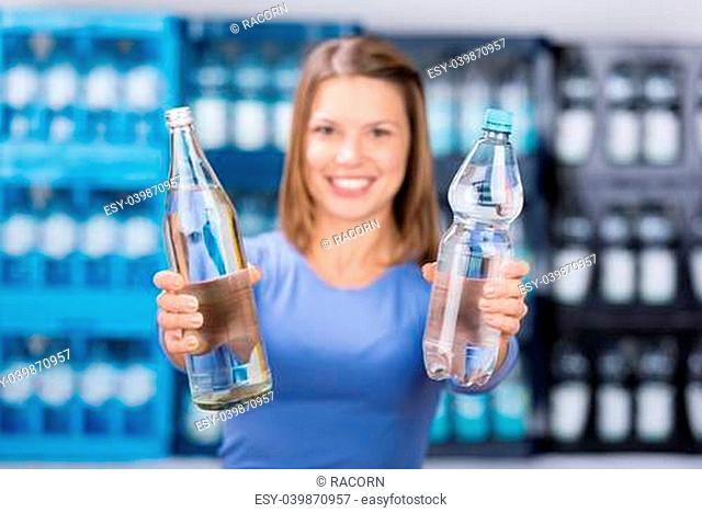 Smiling beautiful female holding a glass and plastic bottle