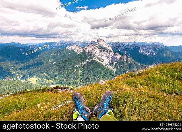 Hiker boots. Rambler having fun and enjoying wonderful breathtaking mountain view. Freedom concept. Italian Alps. Friuli Venezia Giulia