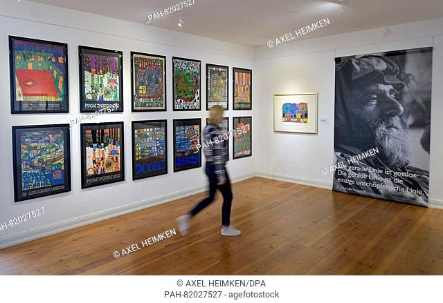 A woman looks at works by and a portrait of artist Friedensreich Hundertwasser in the Ernst Barlach Museum in Wedel, Germany, 13 July 2016