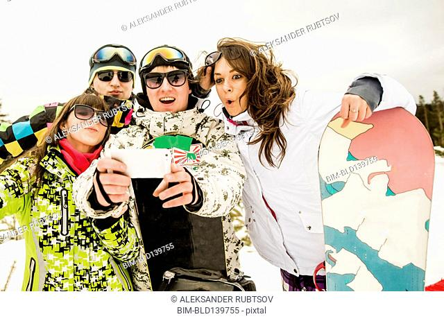 Caucasian friends with snowboard taking selfie