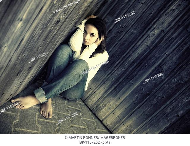 Young sad woman in jeans is sitting in a corner with her back to the wall