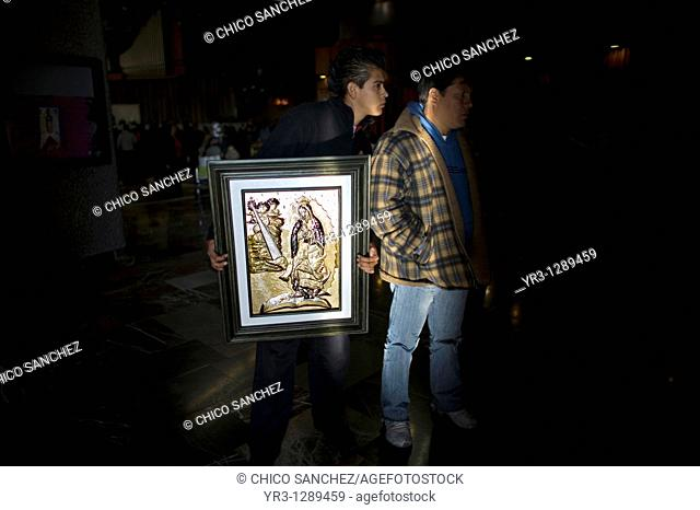 A pilgrim carries an image of the Our Lady of Guadalupe as he walks in the Our Lady of Guadalupe Basilica in Mexico City, December 4