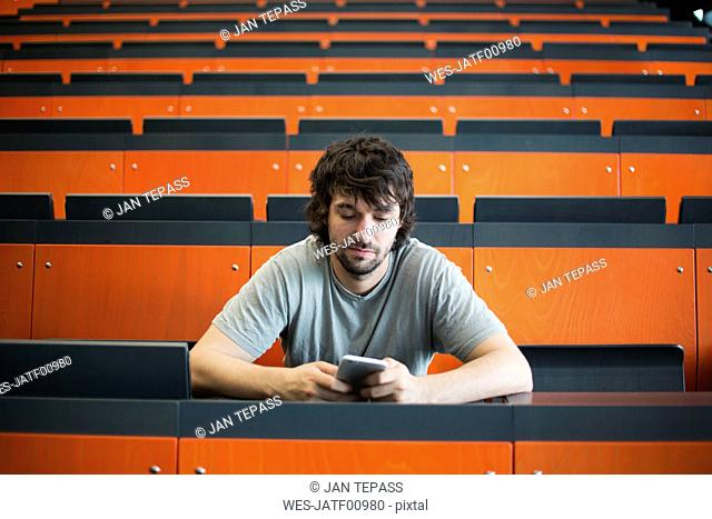 Portrait of student in auditorium at university looking at cell phone