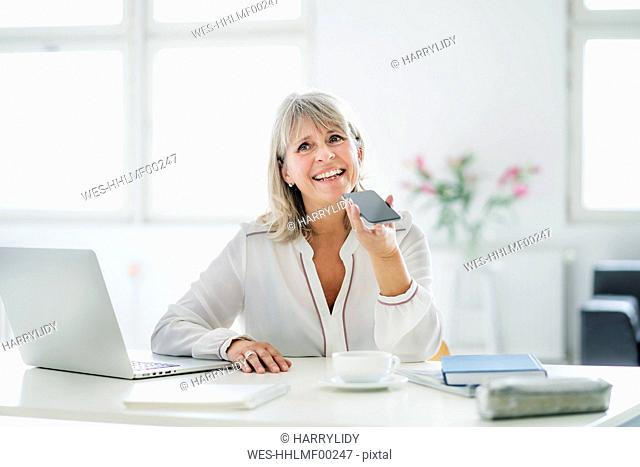 Happy mature businesswoman using cell phone at desk