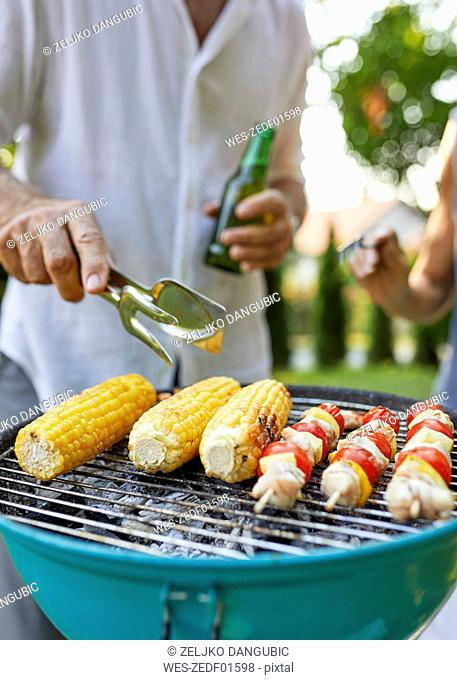Corn cob and meat skewer on grill at barbecue in garden