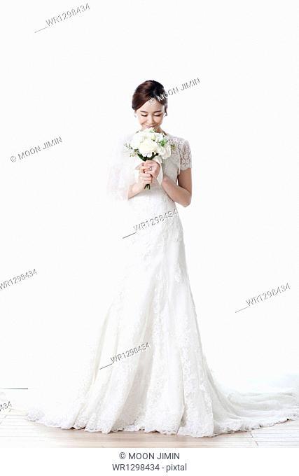 full shot of a woman in wedding dress holding flower bouquet