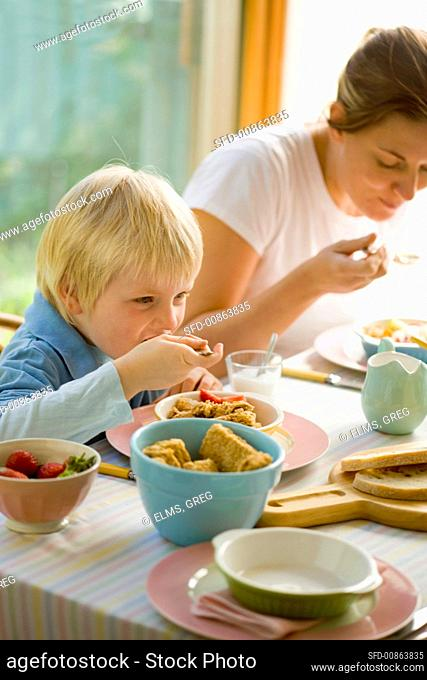 A woman and young boy having breakfast