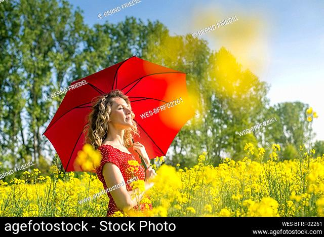 Woman wearing red dress holding umbrella while standing amidst oilseed rapes