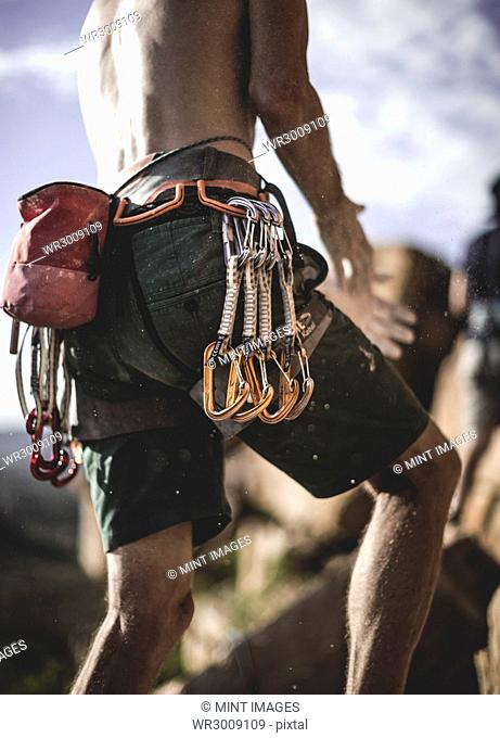 Close up of a mountaineer wearing rope, carabiners, and carabiners on his belt