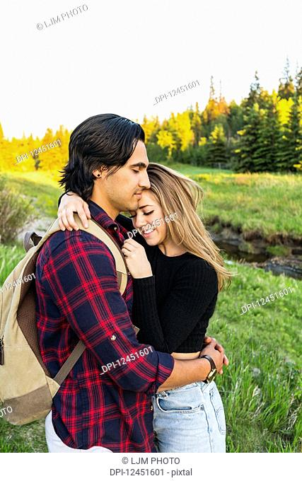Young couple standing in a park in an embrace during a hike in autumn; Edmonton, Alberta, Canada