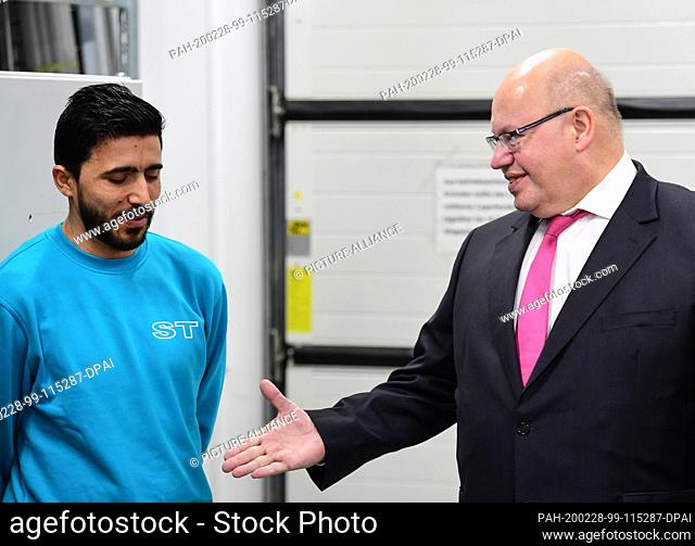 28 February 2020, Brandenburg, Potsdam: Peter Altmaier (r, CDU), Federal Minister of Economics and Energy, shakes hands with the trained electrician and welder...