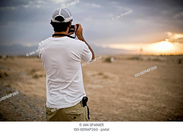 Rear view of man photographing storm cloud in desert, Las Vegas, Nevada, USA