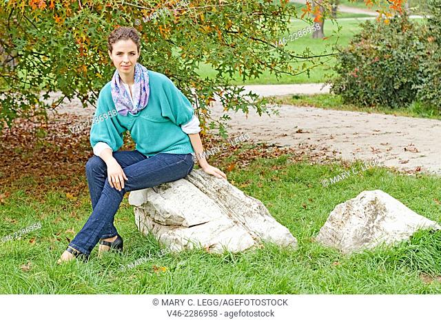 Woman in aqua sweater and blue jeans seated on a rock