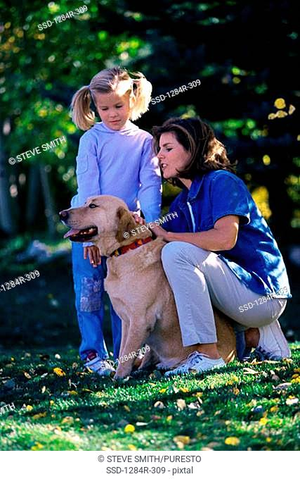 Mother and daughter playing with their pet dog