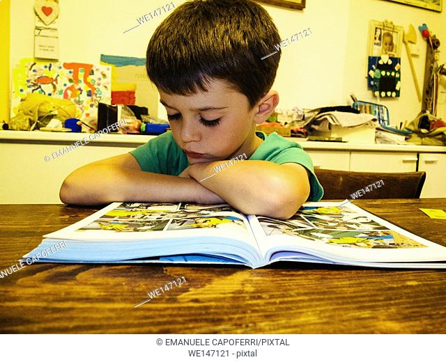 Child reads comics in the kitchen