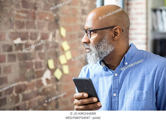 Businessman with cell phone in a loft