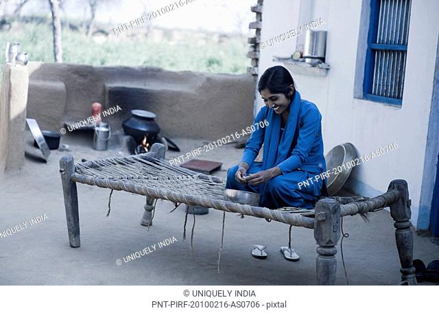 Teenage girl shelling green peas, Farrukh Nagar, Gurgaon, Haryana, India